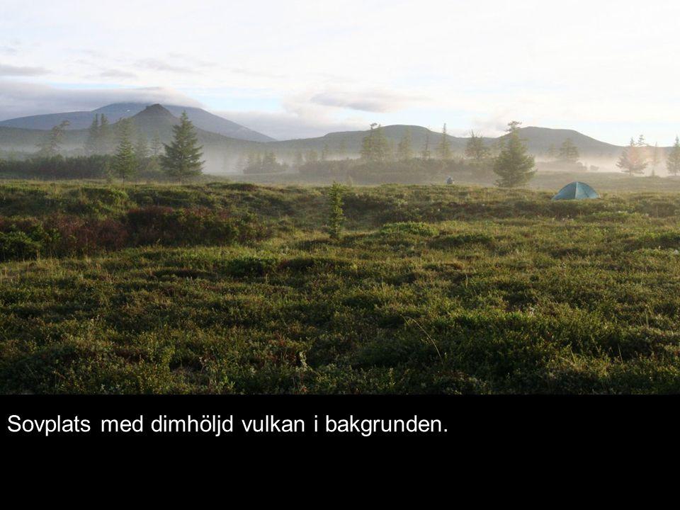 Sovplats med dimhöljd vulkan i bakgrunden.