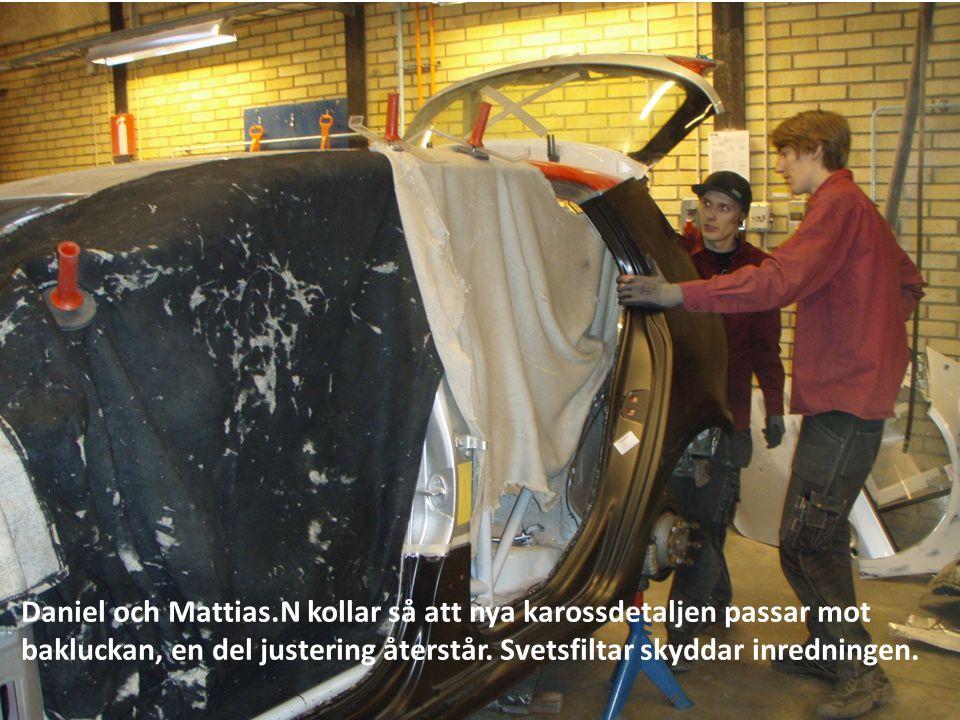 Daniel och Mattias.N kollar så att nya karossdetaljen passar mot bakluckan, en del justering återstår.