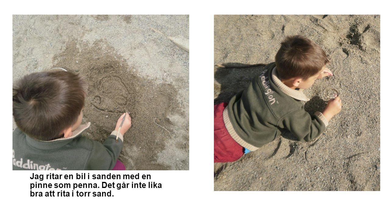 Jag ritar en bil i sanden med en pinne som penna