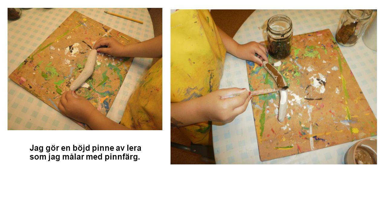 Jag gör en böjd pinne av lera som jag målar med pinnfärg.