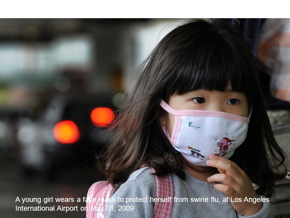 A young girl wears a face mask to protect herself from swine flu, at Los Angeles International Airport on May 01, 2009.