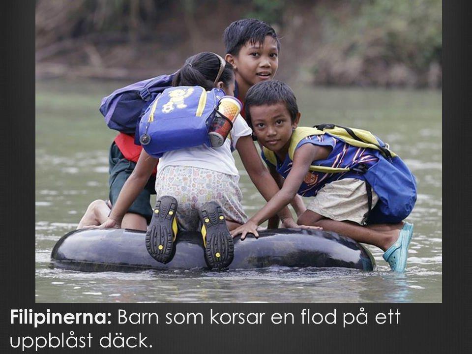 Filipinerna: Barn som korsar en flod på ett uppblåst däck.