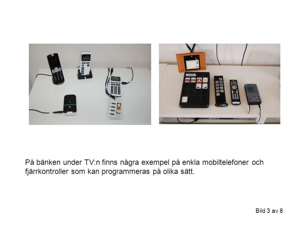 På bänken under TV:n finns några exempel på enkla mobiltelefoner och fjärrkontroller som kan programmeras på olika sätt.